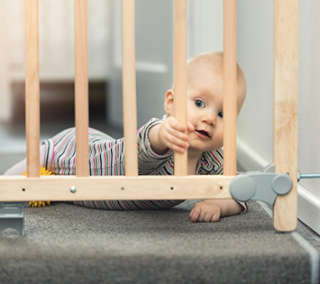 A Baby Held Back By a Childproof staircase Gate, Which Is Part Of Keeping Your Home Safe